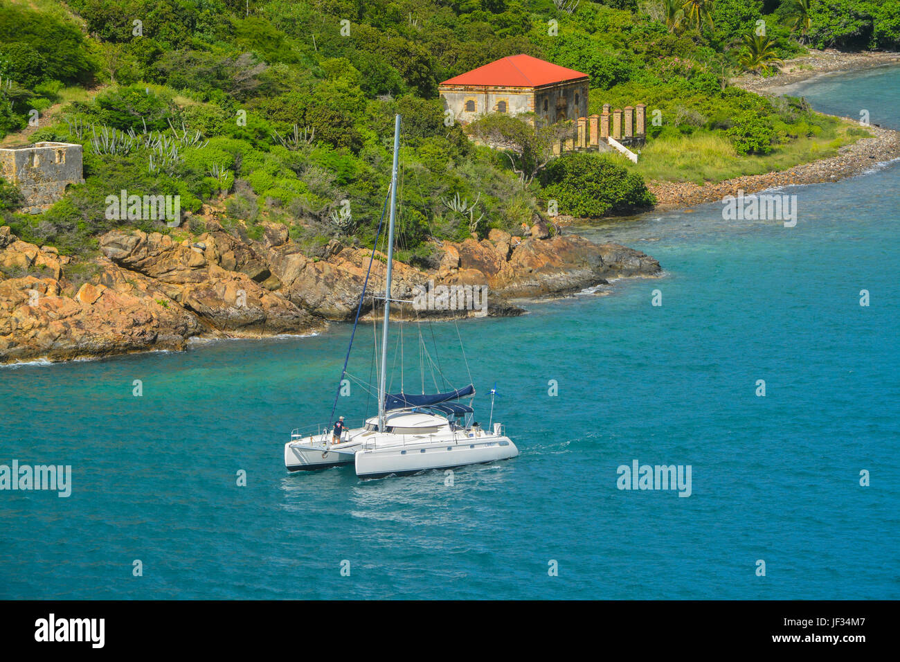 Catamaran sailing by Garrison House at Fort Willoughby on Hassel Island, St Thomas U.S. Virgin Islands. - Stock Image
