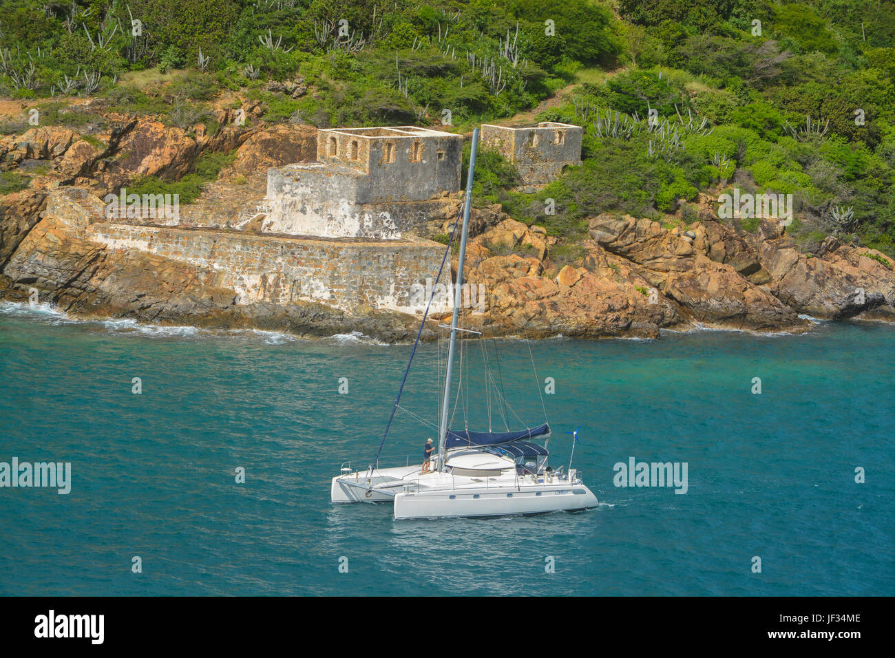 Catamaran sailing by Prince Frederikas Battery. Fort Willoughby on Hassel Island, St Thomas U.S. Virgin Islands. - Stock Image