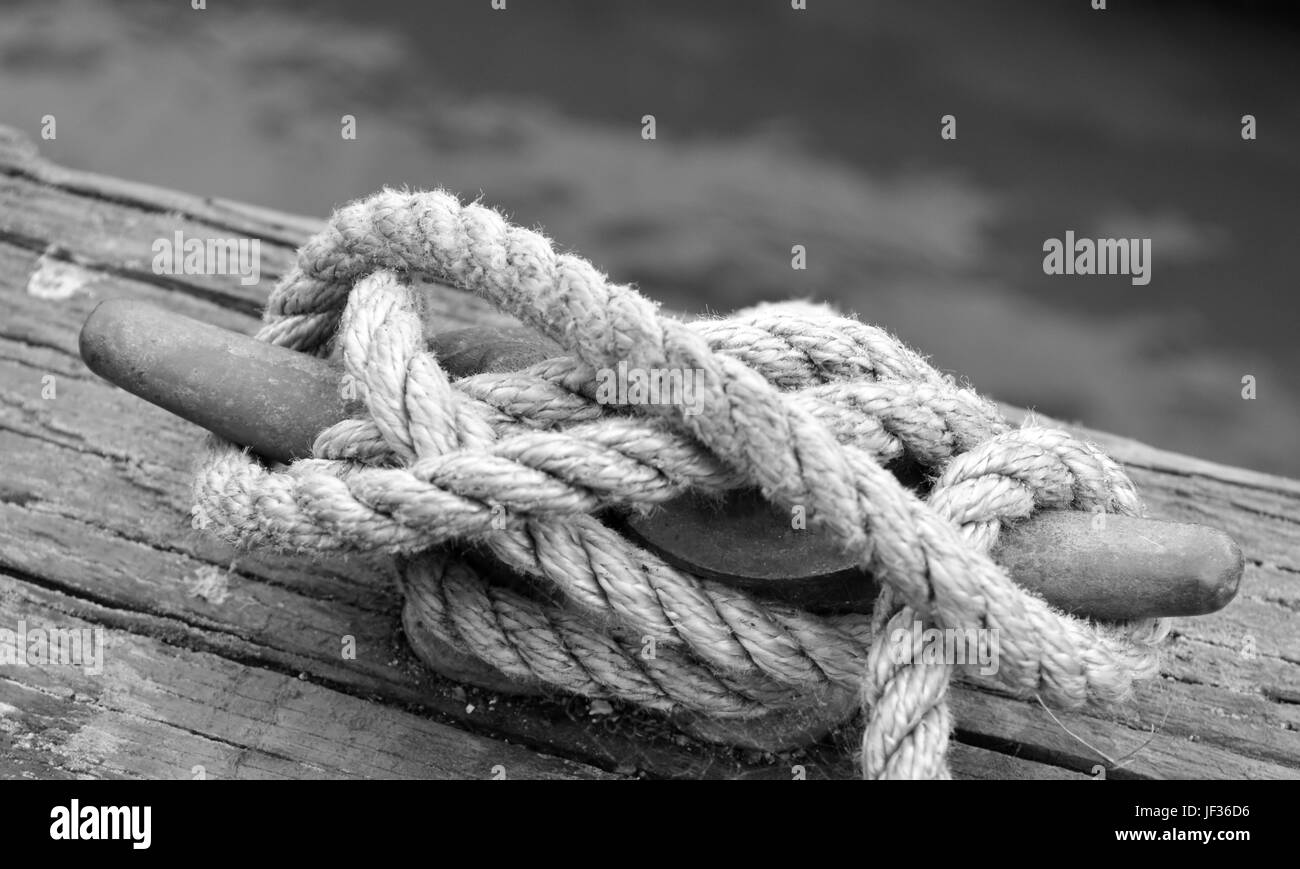 a white used rope fastened on the landing pier - Stock Image