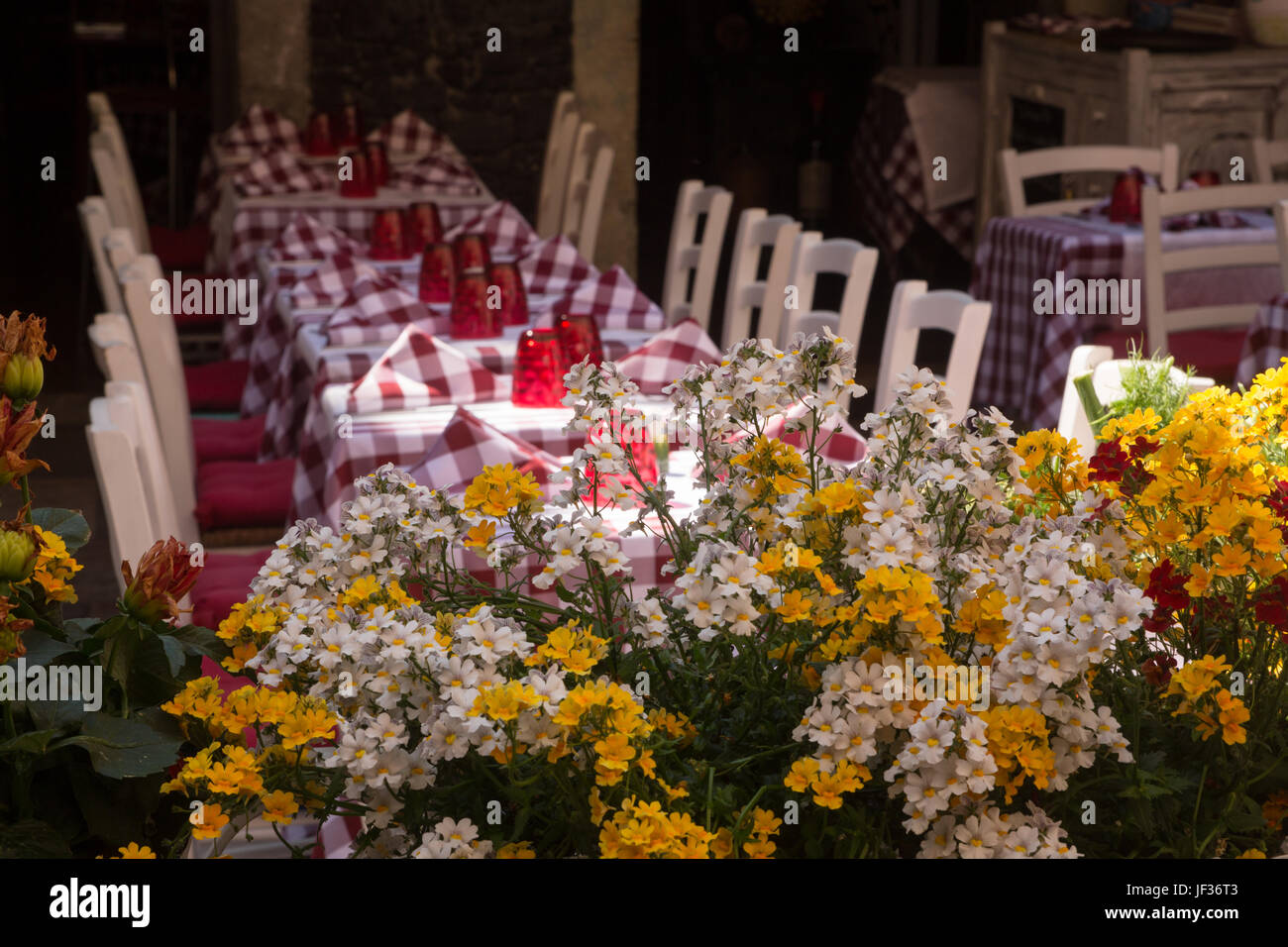 Flowers in front of Al fresco dining tables set with red checked cloths and chairs outside restaurant in Taormina, - Stock Image