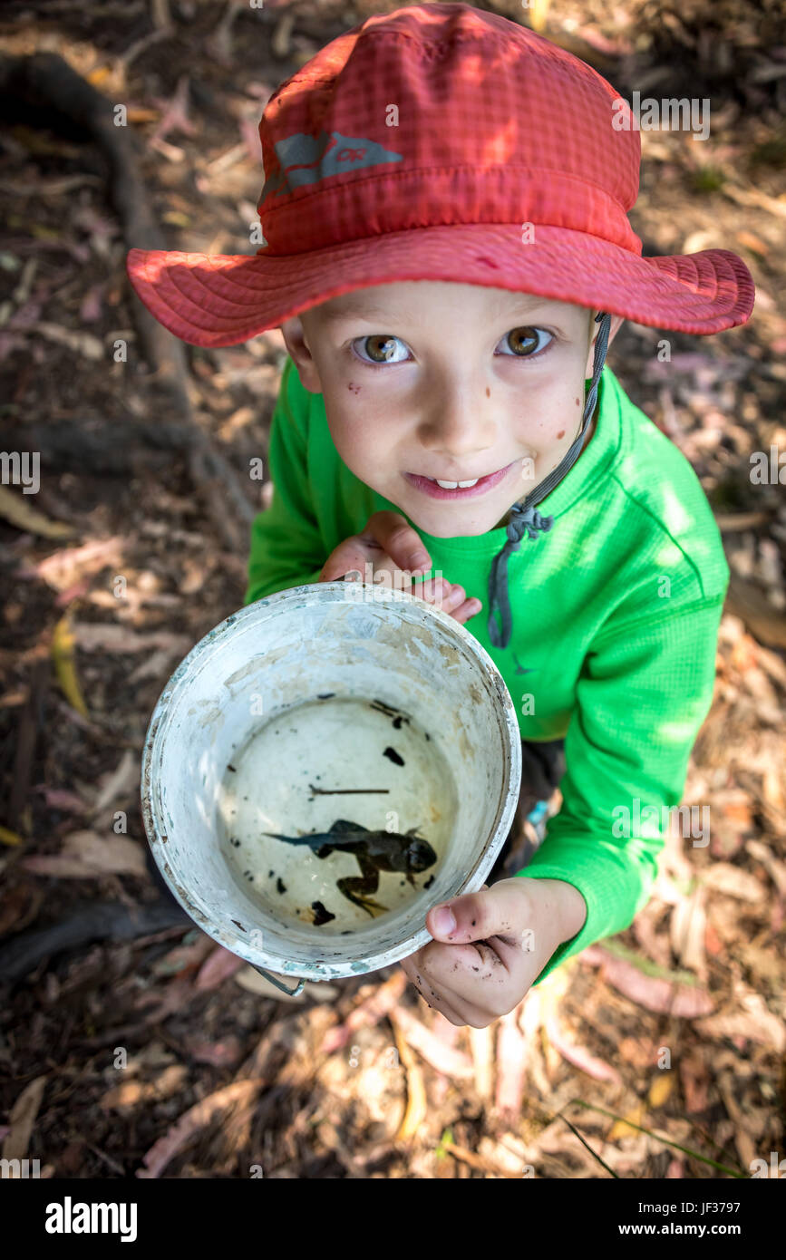 Hiking or camping with kids; a young boy looking up showing a big tadpole / pollywog / frog he found, the frog in - Stock Image