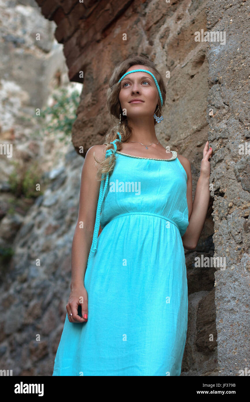 c232180740a Vertical portrait of young blonde woman with braided hear wearing turquoise  dress and touching ancient stone