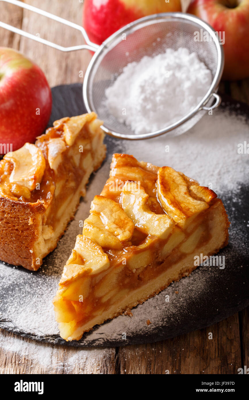 Sliced homemade warm apple pie close-up on a table. vertical - Stock Image