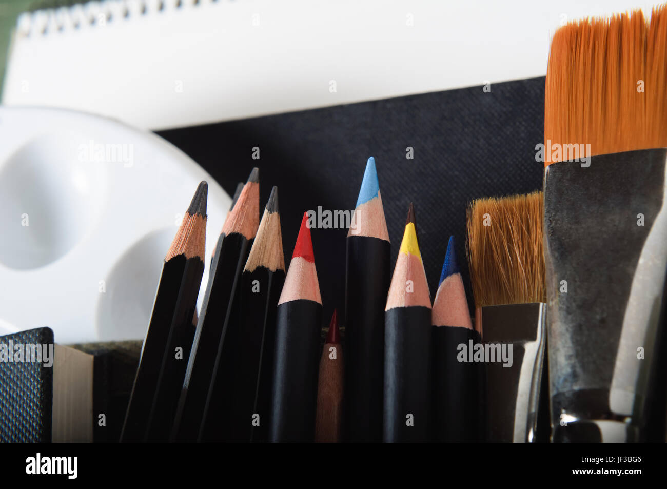 Close up of a selection of artist's tools and materials.  Horizontal (landscape) orientation. - Stock Image