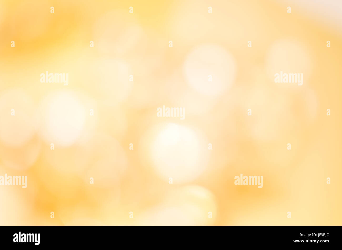 A soft glowing golden yellow bokeh background in landscape (horizontal) orientation. - Stock Image