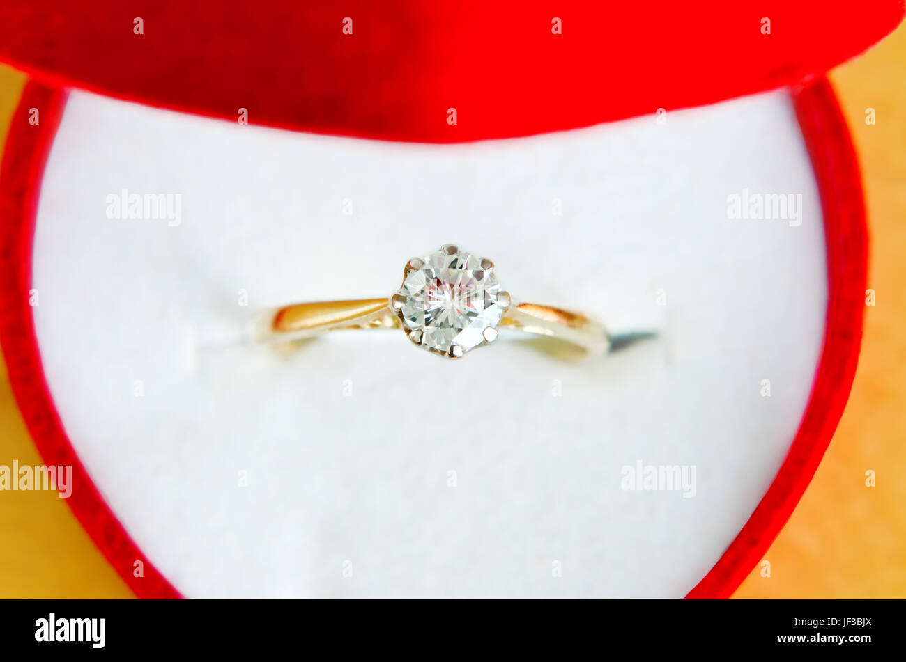 Close up (macro) of  gold, solitaire diamond engagement ring, shot from above, in an open red heart shaped box with - Stock Image