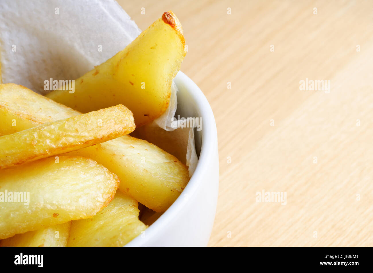 Close up (macro) of a bowl of chips (french fries) nestling on absorbent paper in a white bowl.  Wooden table surface Stock Photo