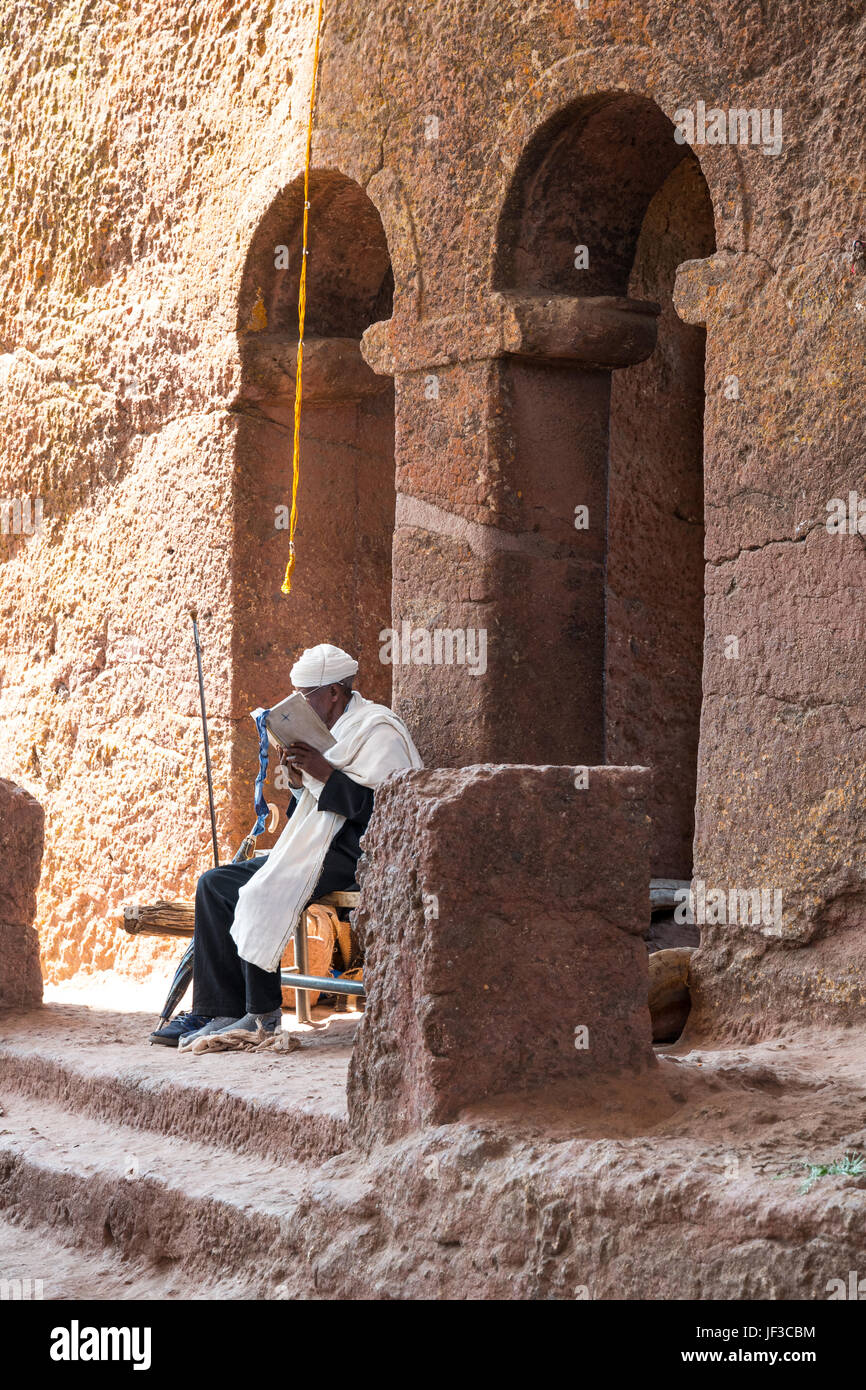 Lalibela, Ethiopia, A priest in prayer at the entrance of the Bet Madane Alem Orthodox church - Stock Image