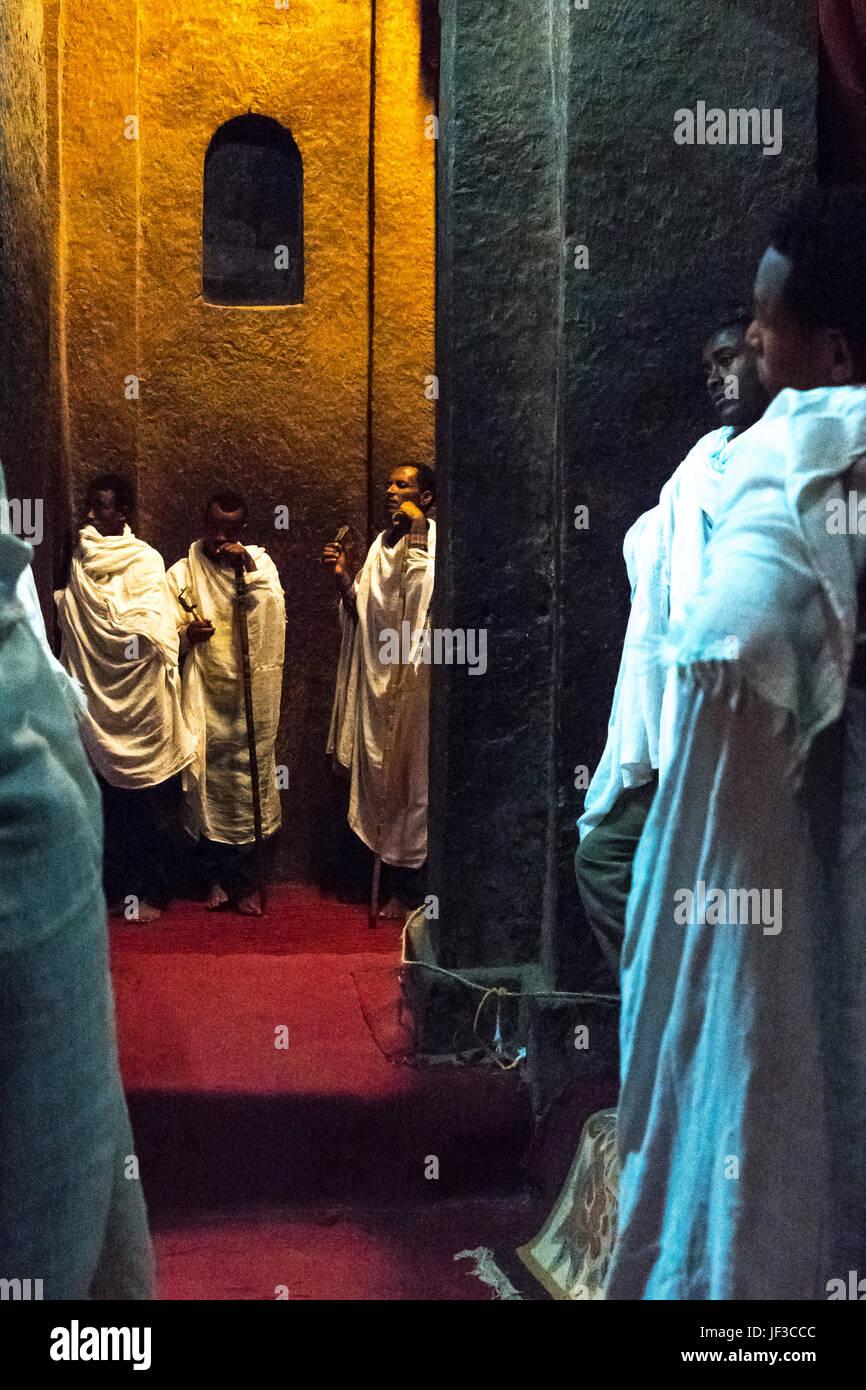 Lalibela, Ethiopia,  Faithfuls and priest in prayer in the dark interior of the Bet Madane Alem Orthodox church - Stock Image