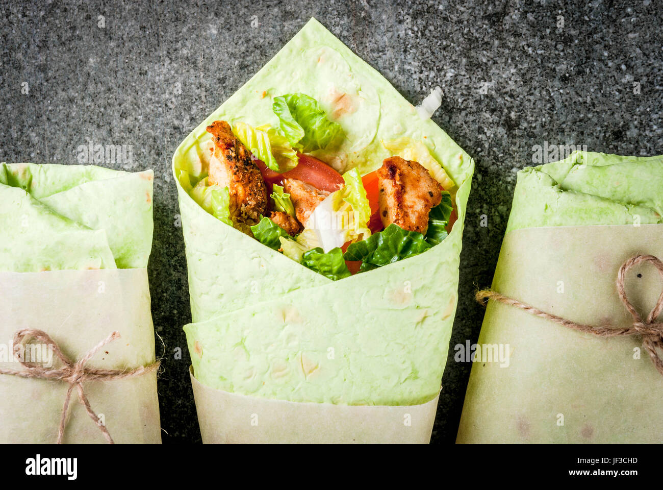 Mexican food. Healthy eating. Wrap sandwich: green lavash tortillas with spinach, fried chicken, fresh greens salad, - Stock Image