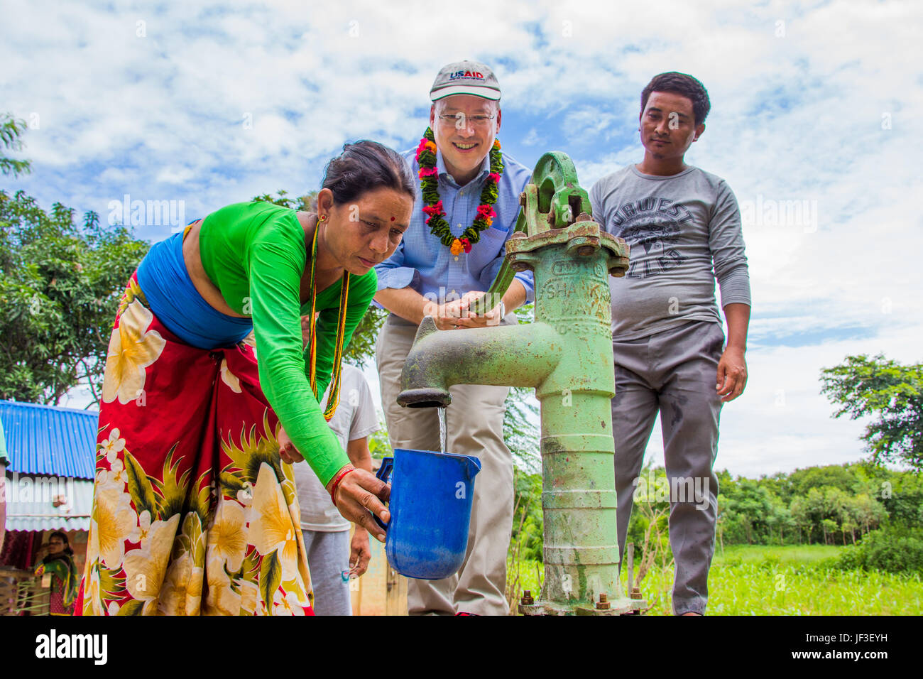 USAID Mission Director Peter Malnak pumping water from a USAID funded community well in the Terai Region of Nepal - Stock Image