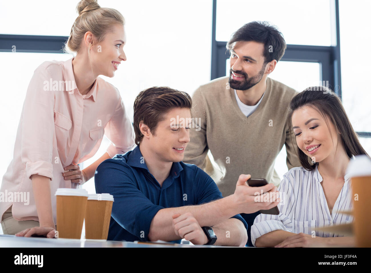 group of young business people using smartphone on small business meeting - Stock Image