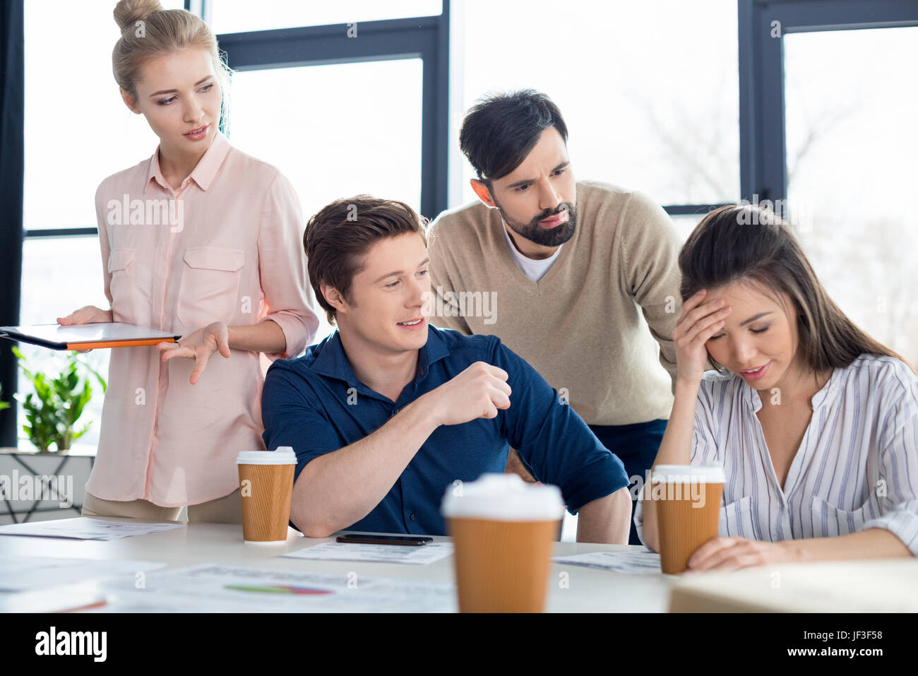 group of young business people looking at colleague on small business meeting - Stock Image
