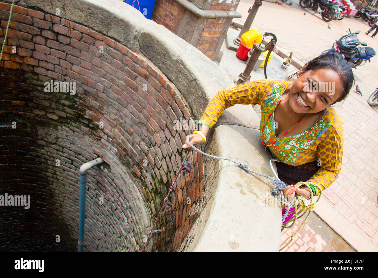 Young woman drawing water from a well in Bhaktapur, Kathmandu, Nepal - Stock Image