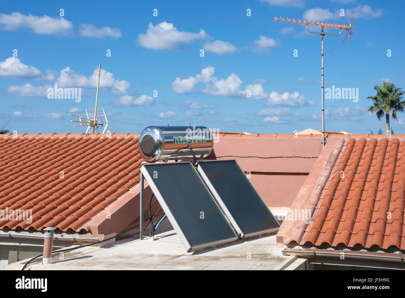 Solar panels and hot water cylinder on roof of apartment building, Rethymno (Rethymnon), Rethymno Region, Kriti (Crete) Region, Greece