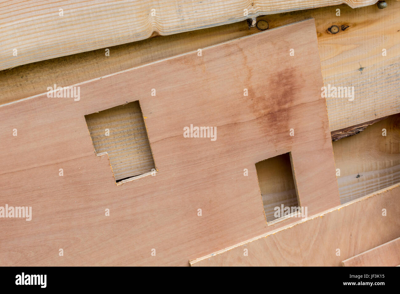 Section of plywood with square holes cut out - possible metaphor for DIY and home improvement. - Stock Image