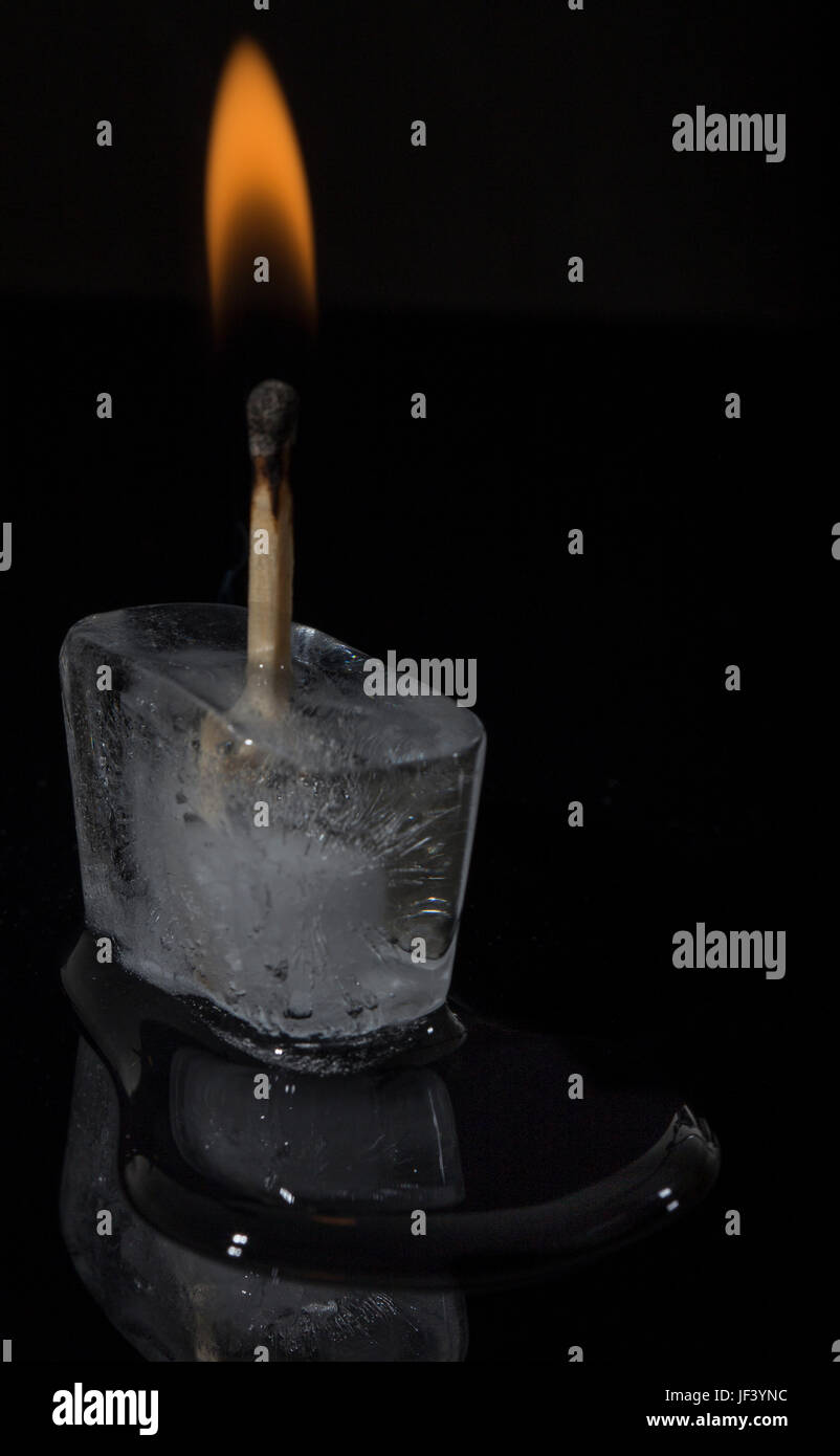 A lit match frozen inside an ice cube on a black acrylic surface. - Stock Image