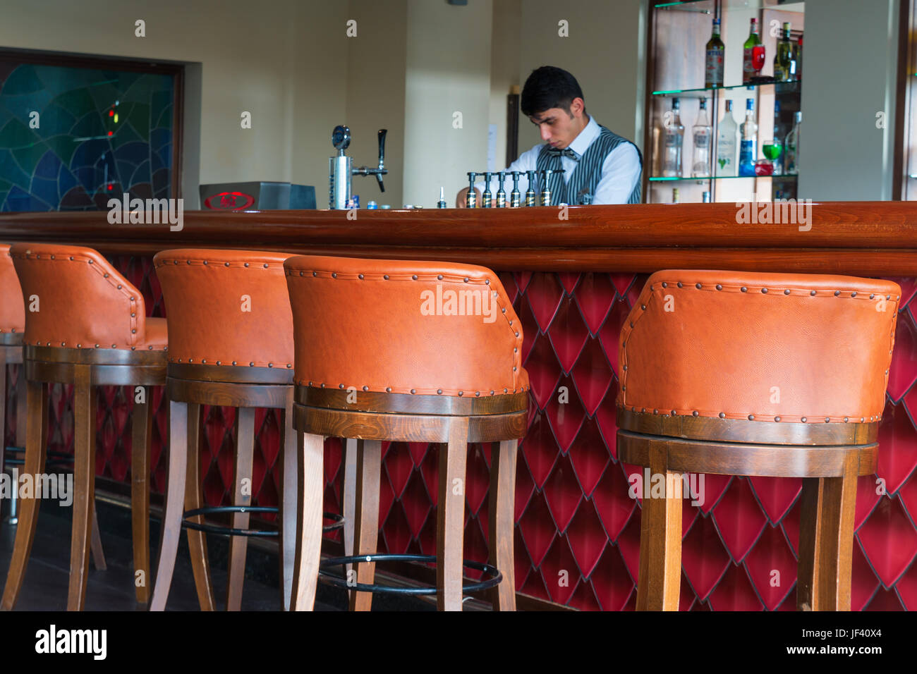 Arabic barman behind counter, preparing something to drink. - Stock Image