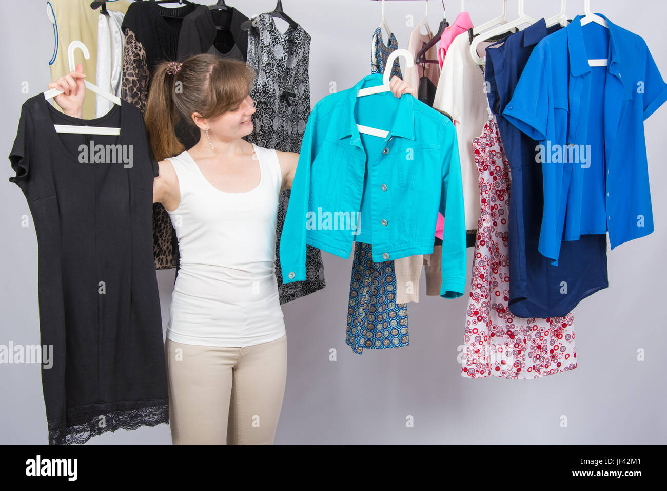 Girl chooses clothes in her wardrobe - Stock Image