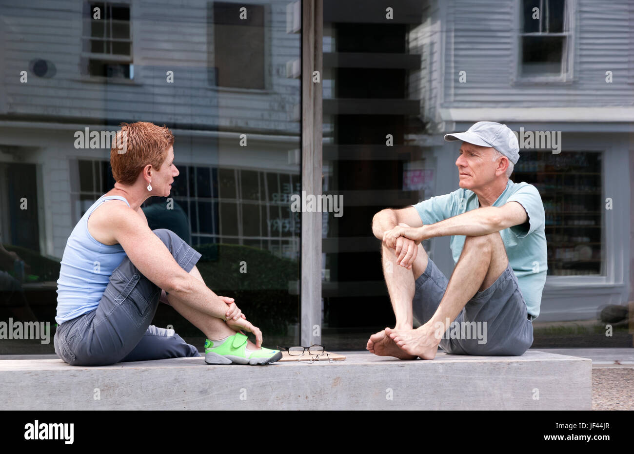 Two adults sitting and having a conversation while sitting on a ledge outdoors. - Stock Image