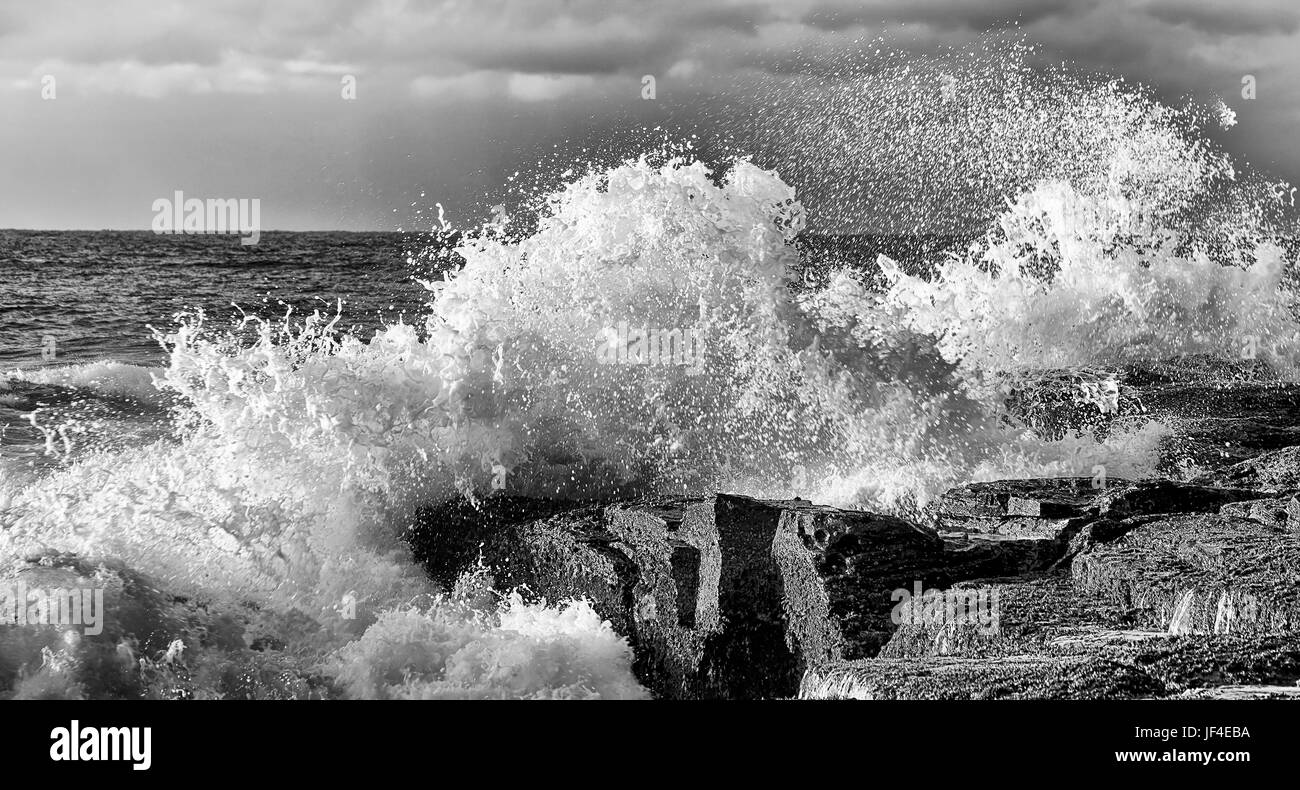 Dramatic stormy waves hit sandstone rocks at Sydney northern beaches coast of Pacific ocean. Rolling mighty waters - Stock Image
