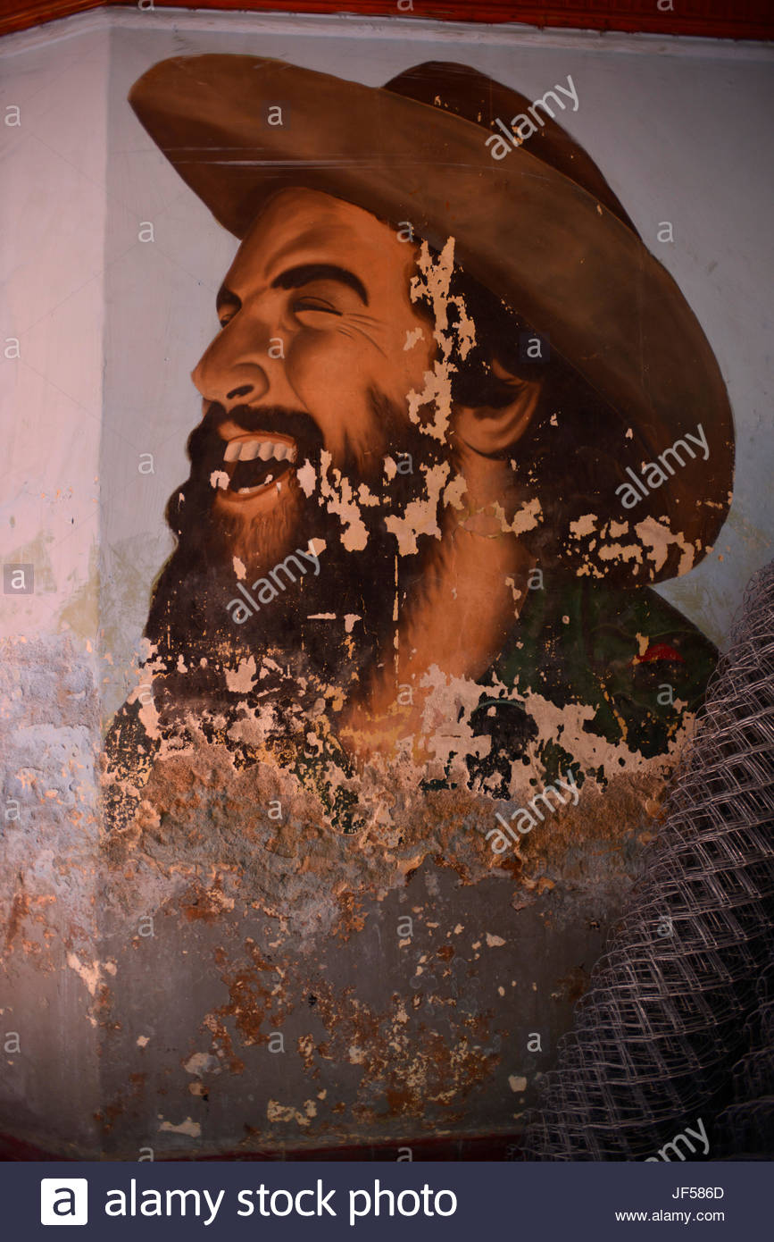A distressed portrait of Camilo Cienfuegos Gorriaran, a Cuban revolutionary, on the wall of a building. - Stock Image