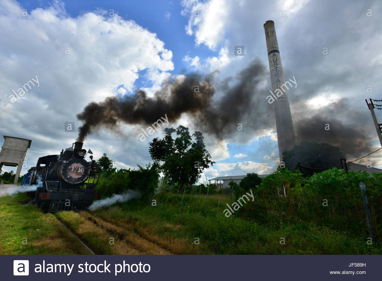 A 1913 steam locomotive that was used in the transport of sugarcane steams past a disused sugar factory smokestack. - Stock Image