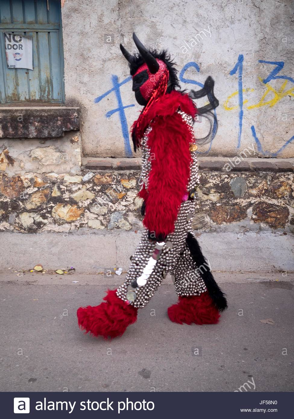 A person walks down a street wearing a devil costume for the Day of the Dead celebration. Stock Photo