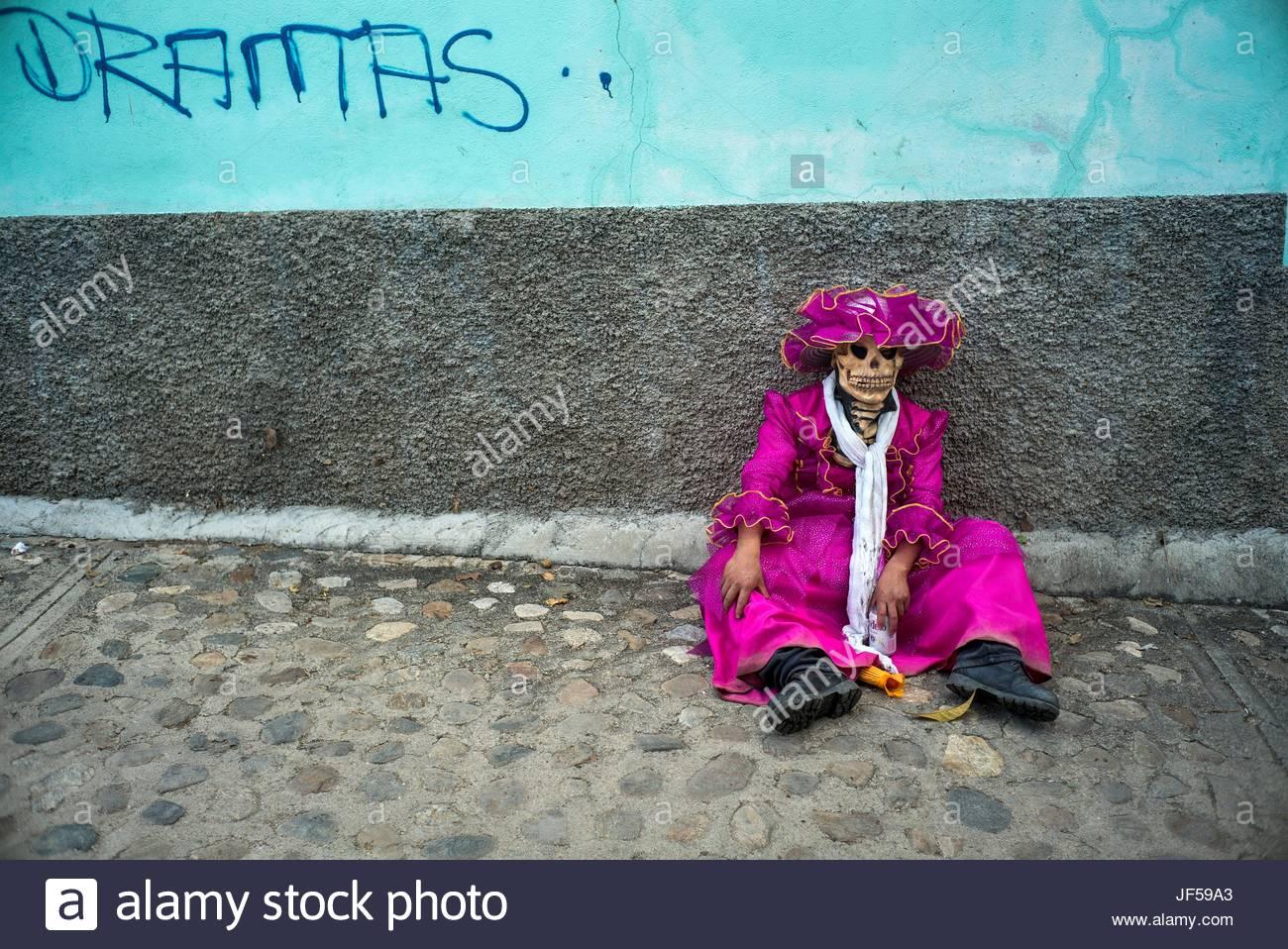 A drunk and tired participant rests in a street during a Day of the Dead celebration. - Stock Image