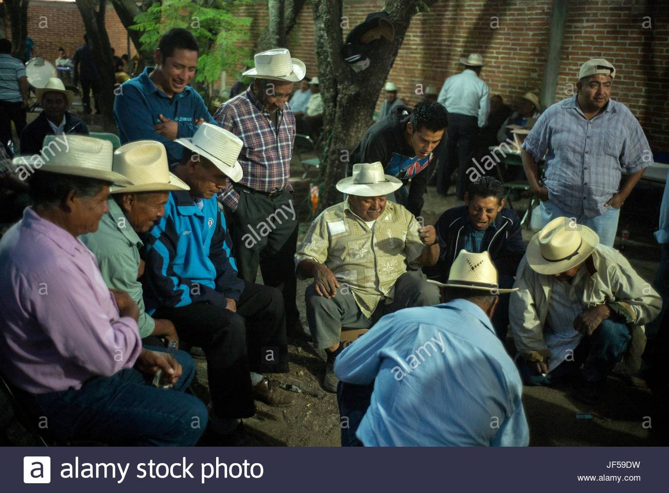 Men play dice in a cemetery during the Day of the Dead celebration. - Stock Image