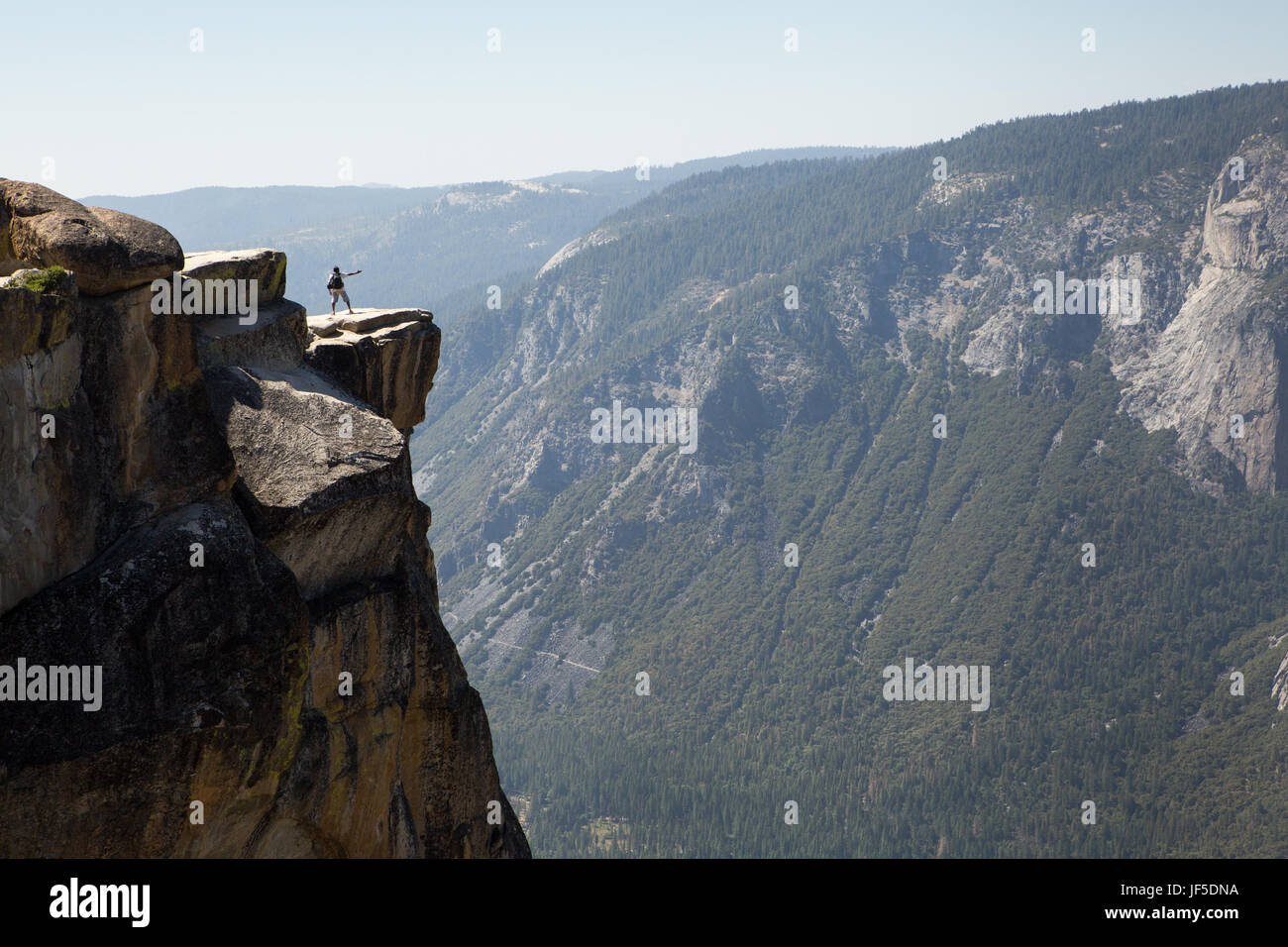 A visitor to Yosemite National Park stands on a rock ledge at Taft Point. This ledge, at an elevation of about 7,500 - Stock Image