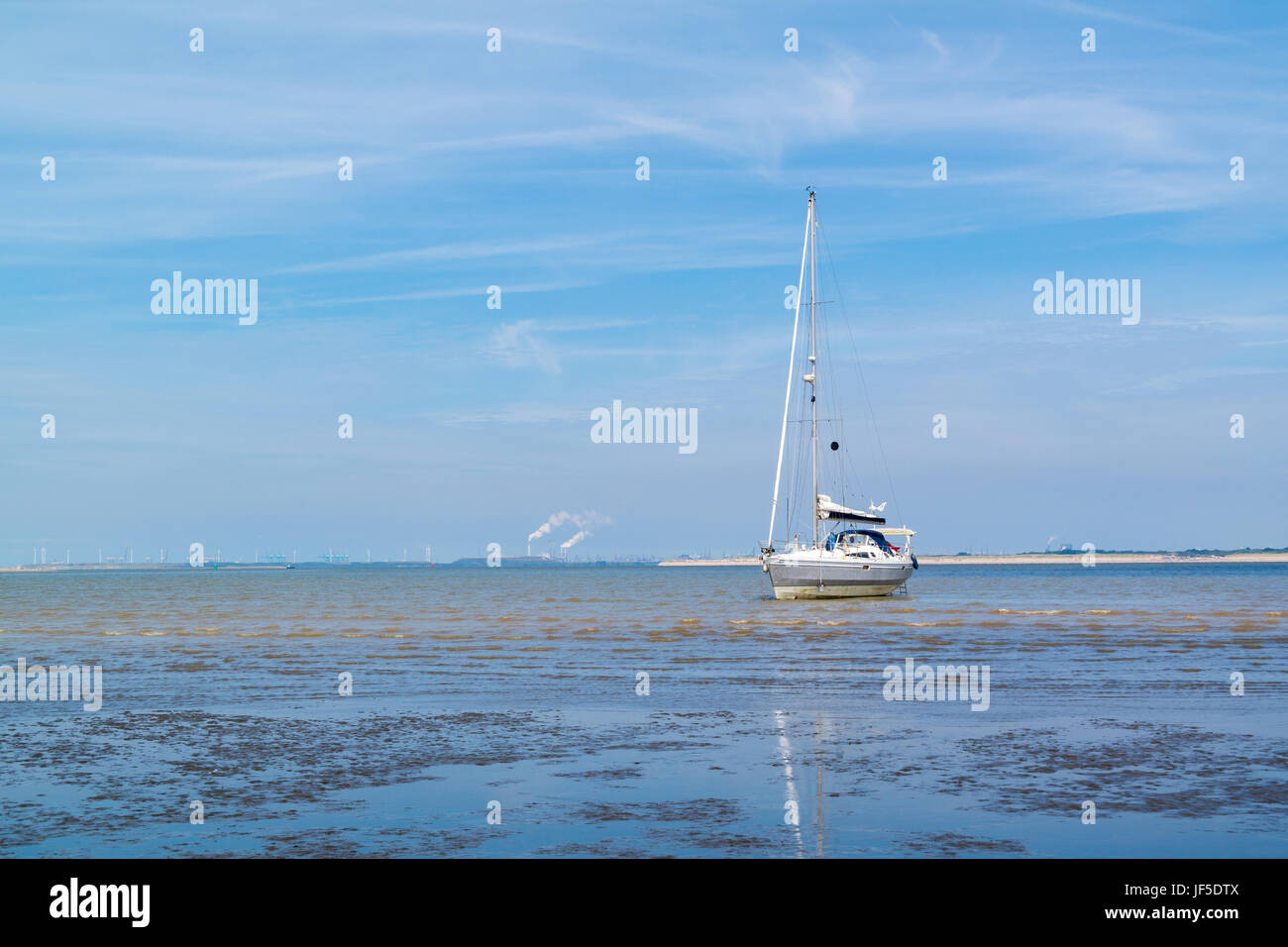 Sailboat aground on sandflat at low tide near Maasvlakte and port of Rotterdam, South Holland, Netherlands - Stock Image