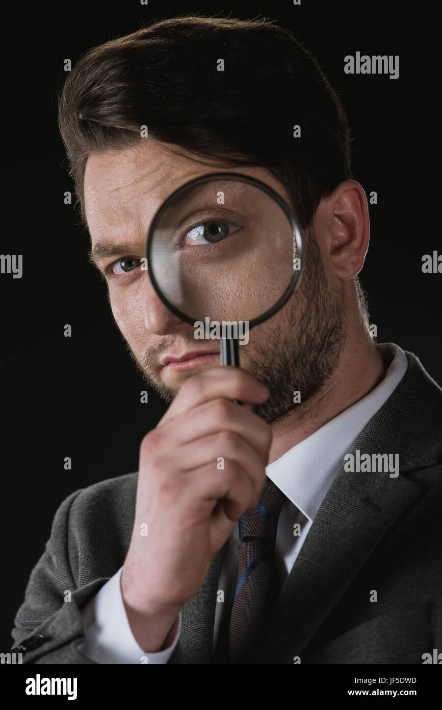 portrait of businessman holding magnifying glass isolated on black Stock Photo