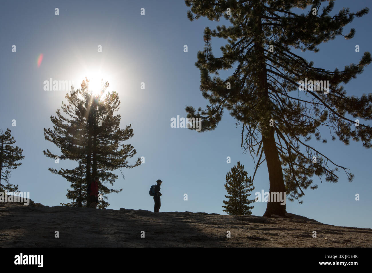 A hiker pauses on the rocky trail that leads to Sentinel Dome, a rocky peak that offers stunning views to the Yosemite - Stock Image