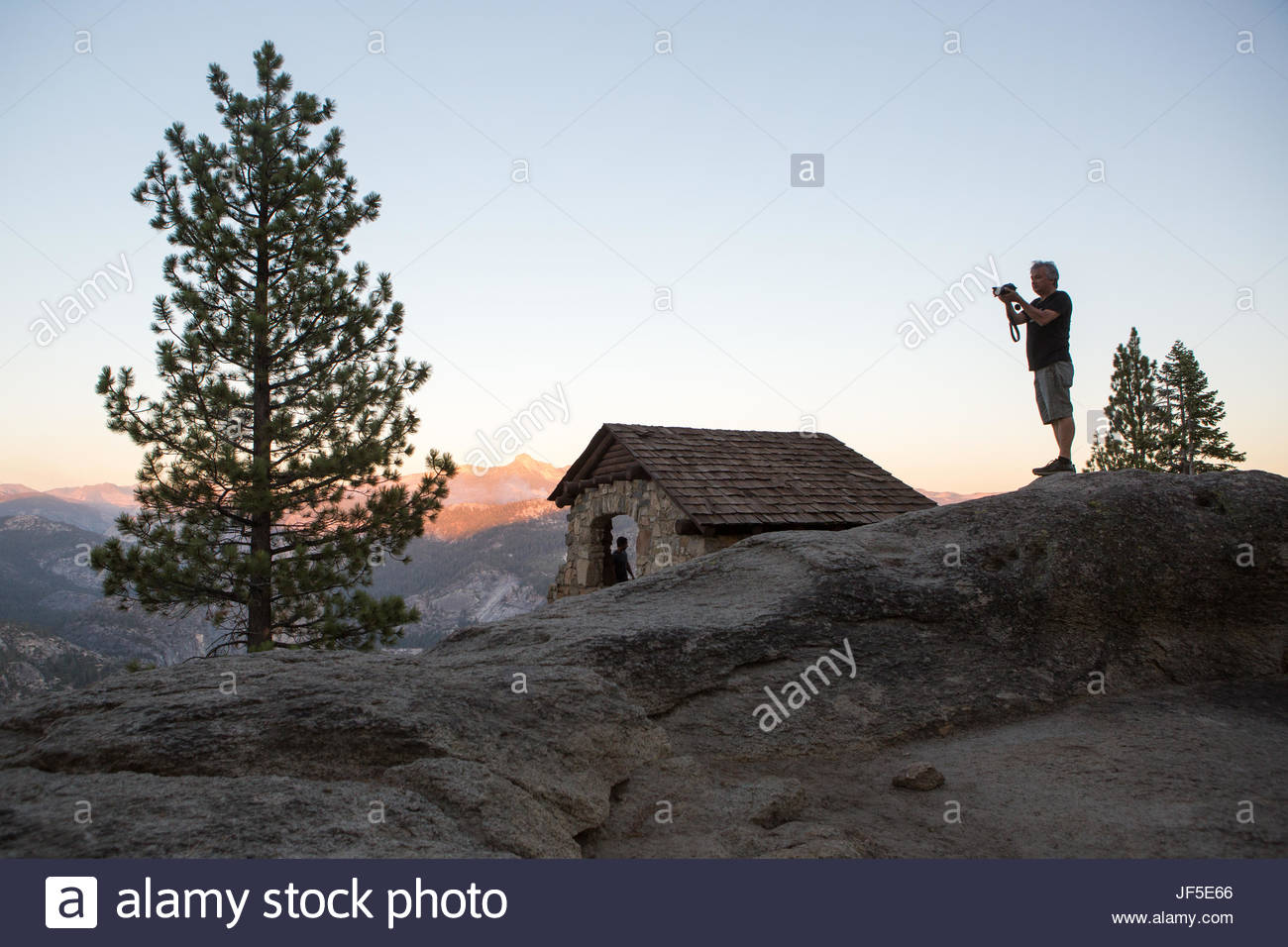 A hiker at Glacier Point takes a moment to photograph his surroundings. - Stock Image