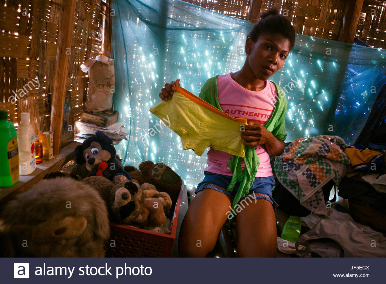 Alvina, formerly Alvin, a transgendered male Ayta holds up a pair of shorts. Access to mainstream media and the - Stock Image