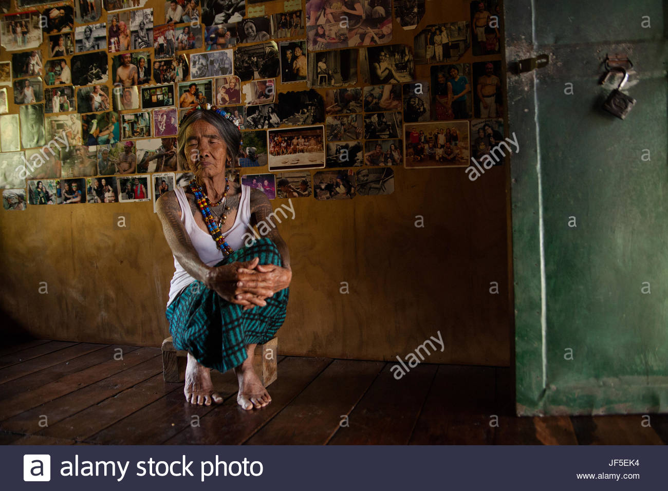 Fang Od, the last traditional tattoo artist in Kalinga, sits by her wall of photographs given by tourists. Modernity - Stock Image