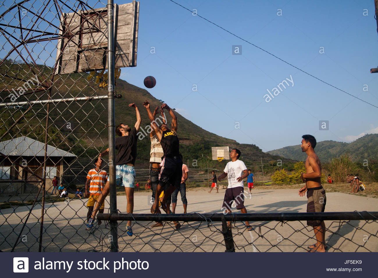 A French traveler playing basketball with the men of the Butbut tribe. The traditional way of tattooing has made - Stock Image