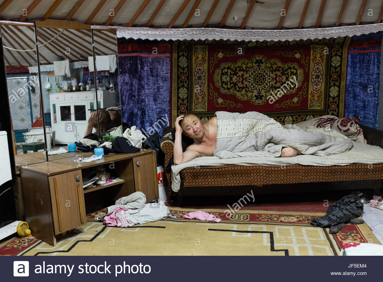 A nomad man rests inside his Mongolian ger. The furnishing inside his ger is comprised of both Mongolian patterned - Stock Image