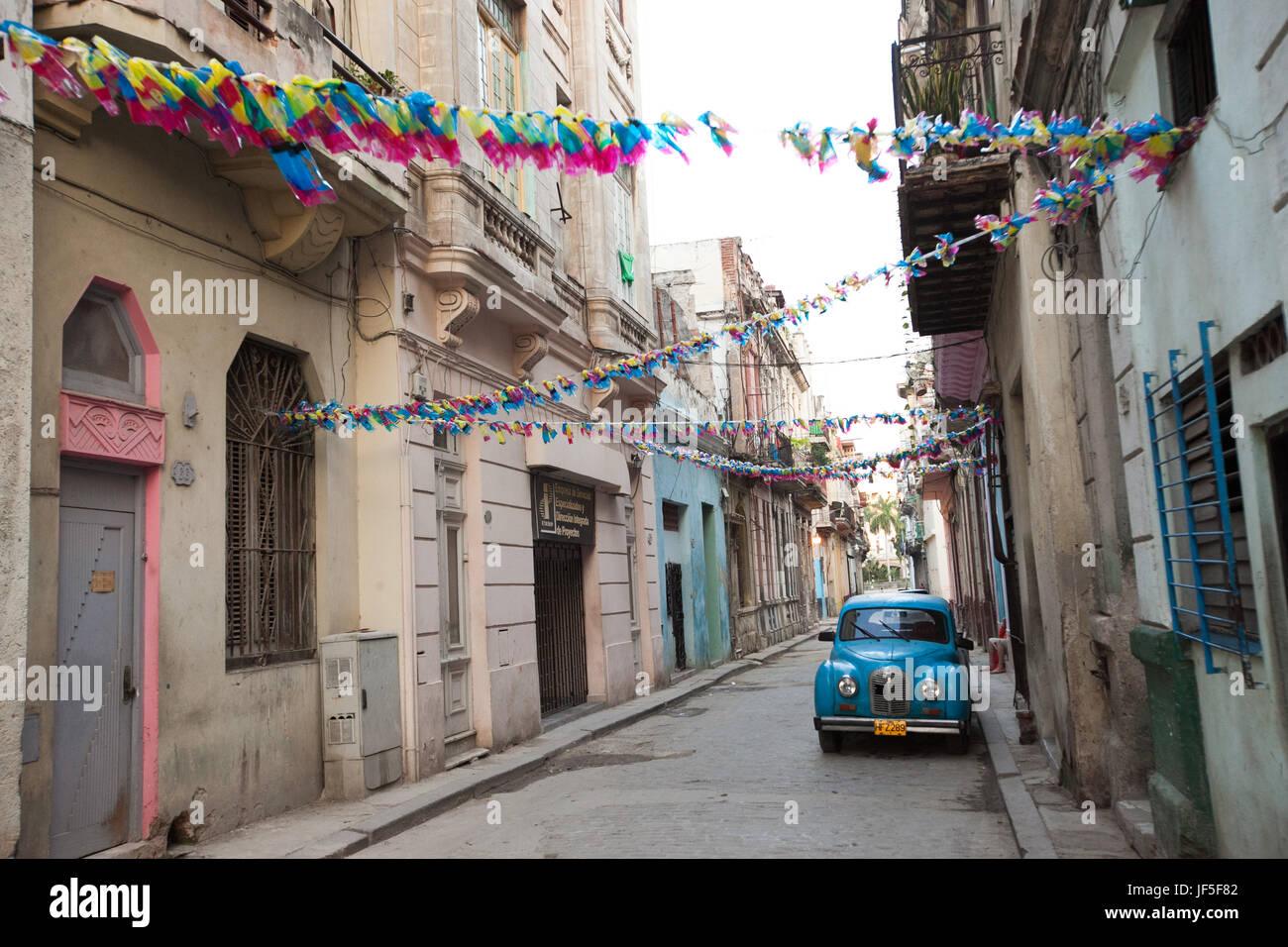 Above a classic American car, colorful decorations hang from buildings on a narrow street in downtown Havana. - Stock Image