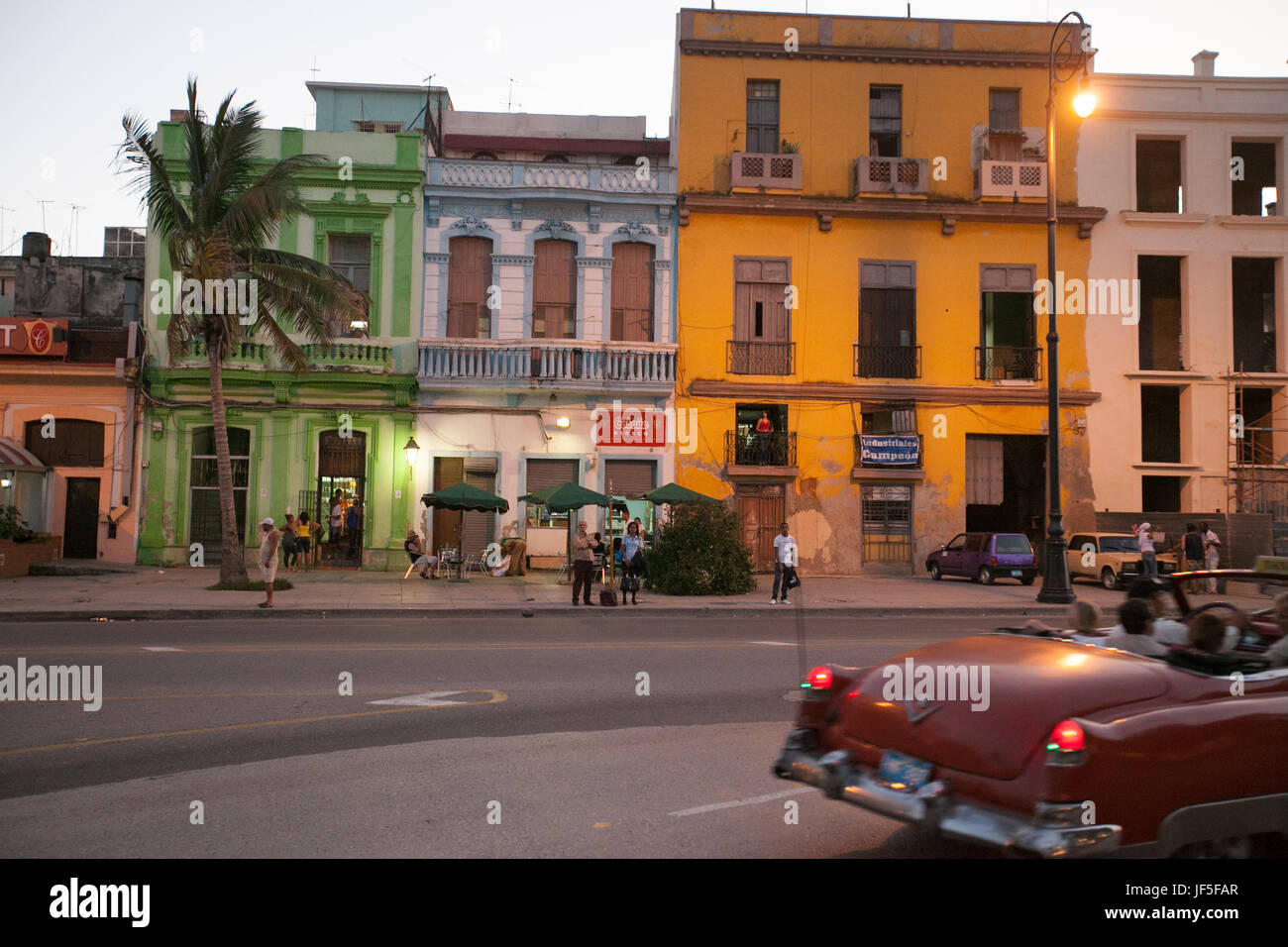 At dusk, people stand on the street as a classic American car drives by in downtown Havana. - Stock Image
