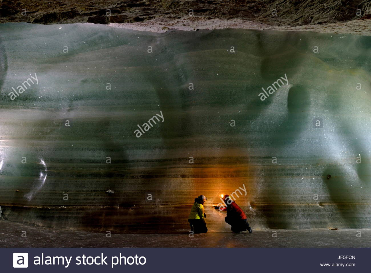 Scientists examine the thick bed of ice for samples inside Eisriesenwelt Eishoehle in Werfen, Austria. - Stock Image