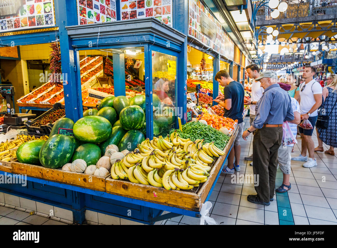 Colourful fruit stall with attractive display of bananas, melons and fruits in the covered Central Market Hall (Vasarcsarnok), Stock Photo