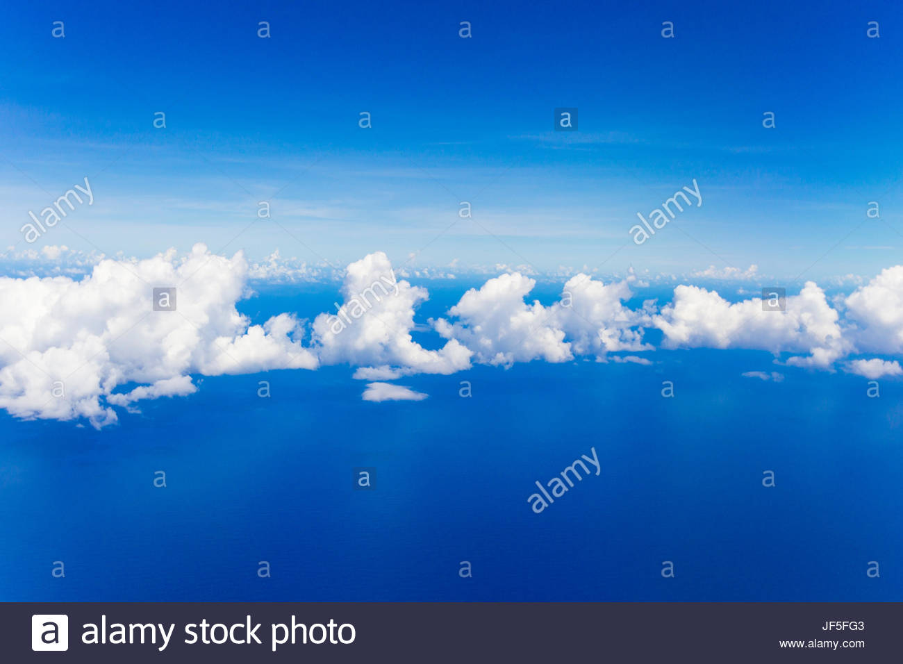 Cumulus clouds floating above flat calm seas on the Atlantic Ocean, somewhere near the Bahamas. - Stock Image