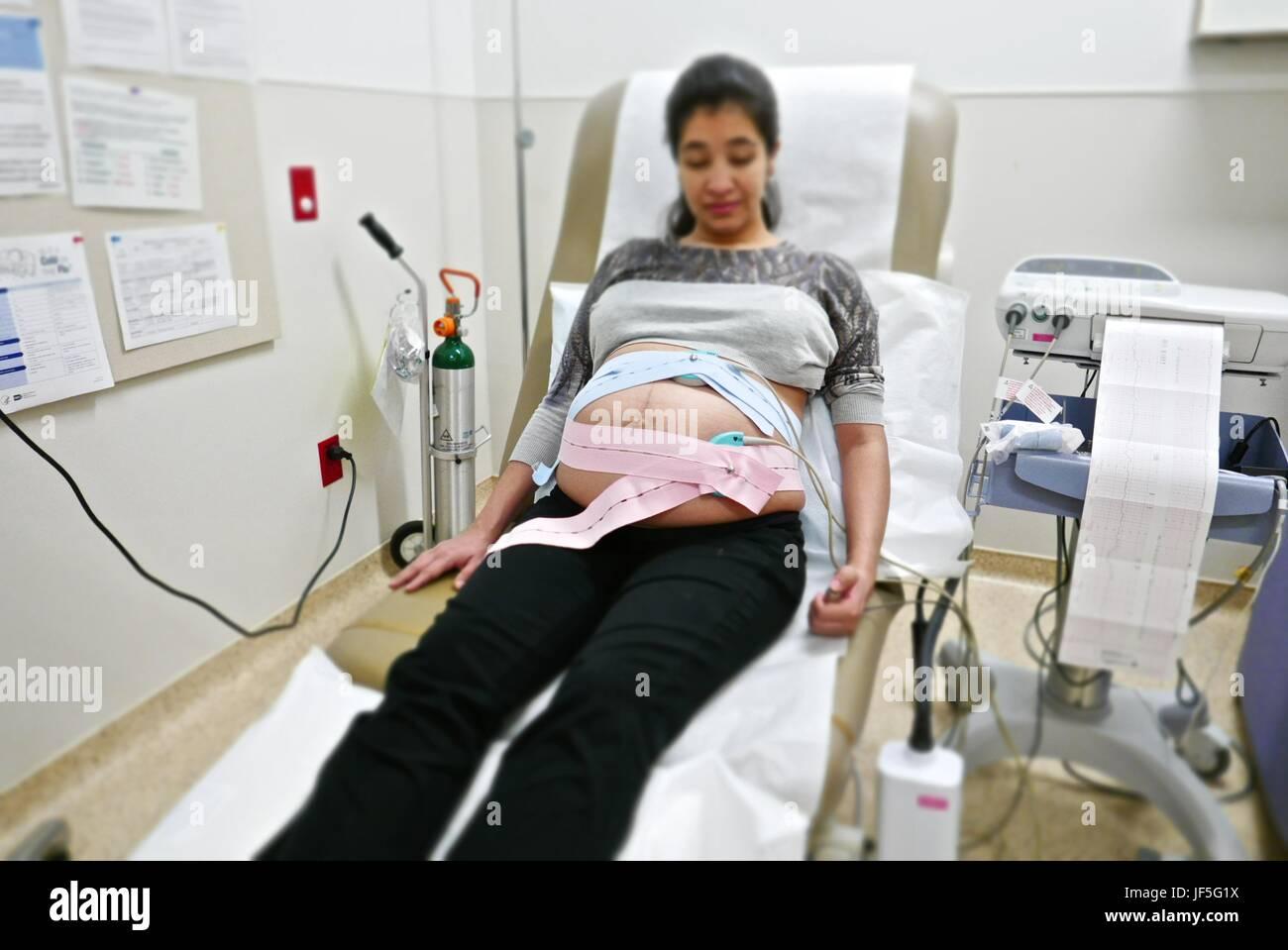 A 41-week pregnant Hispanic woman having a fetal non-stress test, NST. - Stock Image