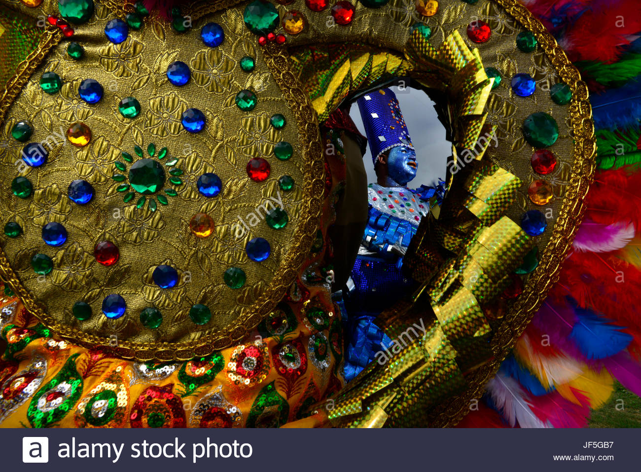 A glitzy hat and costumed people during Carnival. - Stock Image