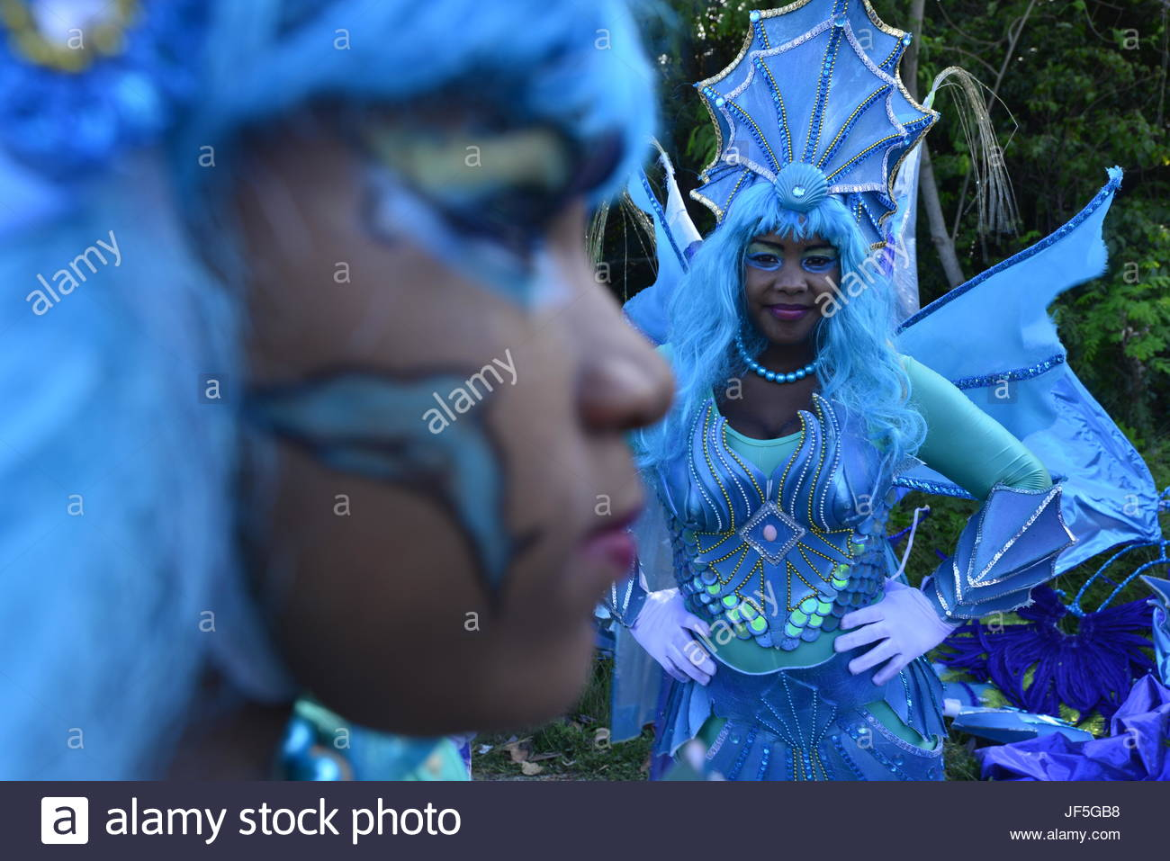Women wearing glitzy blue costumes and headgear during Carnival. - Stock Image