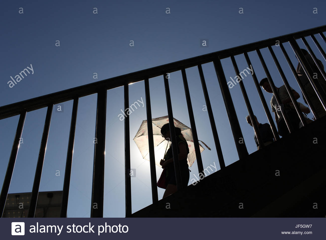 A woman with an umbrella walks down a flight of stairs in Beijing. - Stock Image