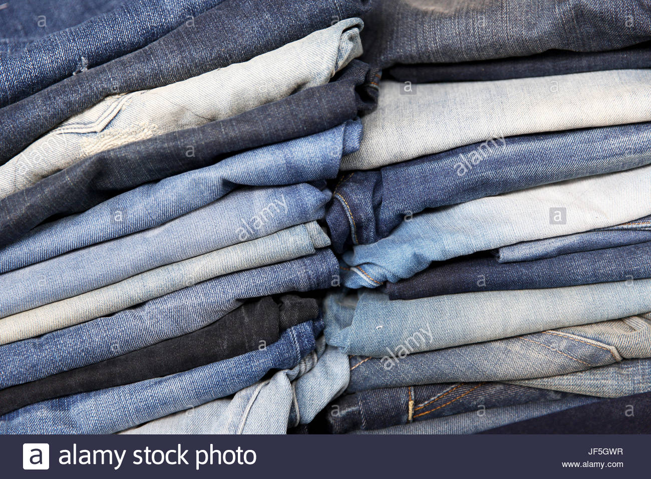 Jeans stacked in a showroom at a denim factory. - Stock Image