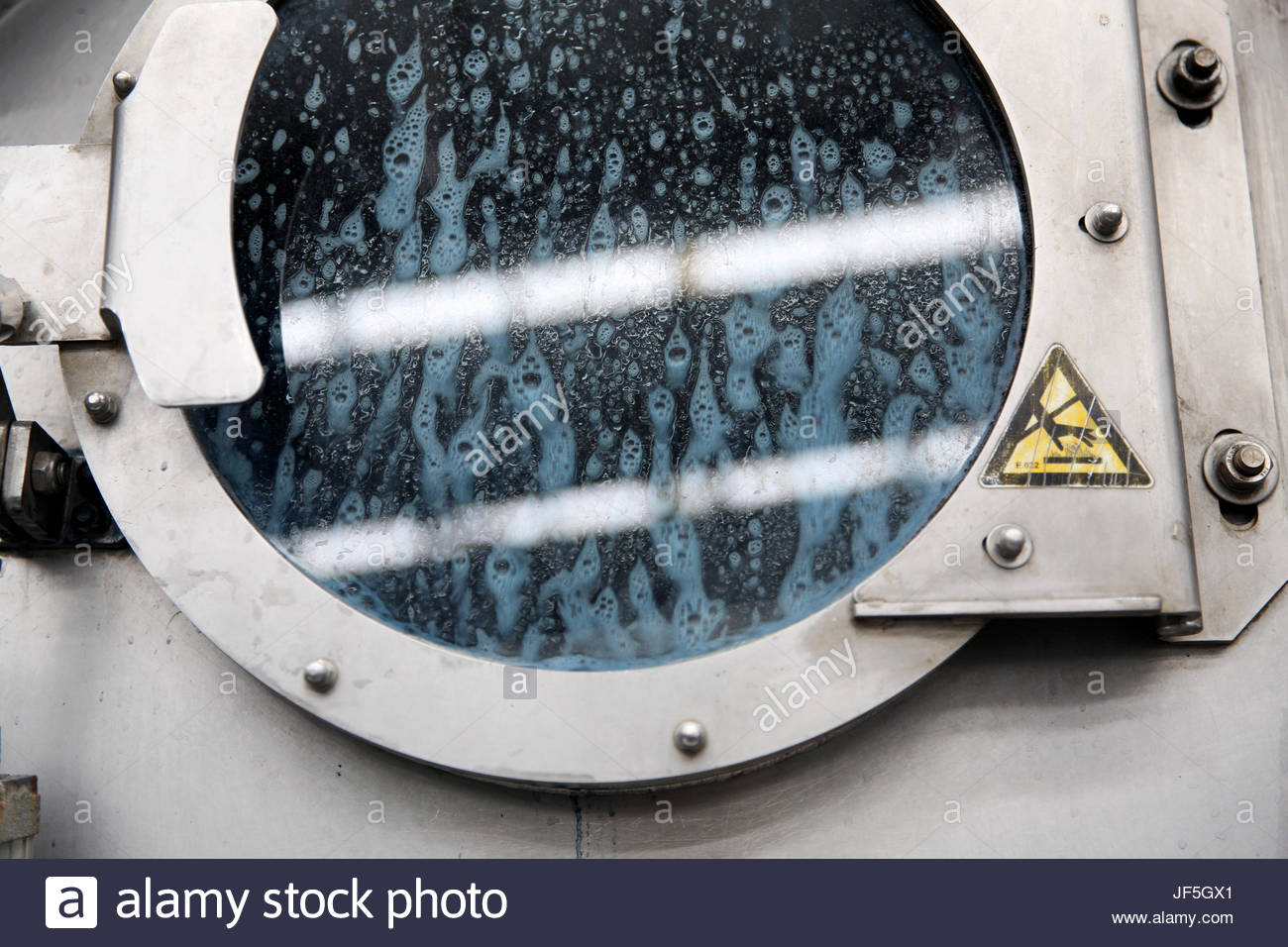 Jeans being washed in large washing machines at a modern denim factory. - Stock Image
